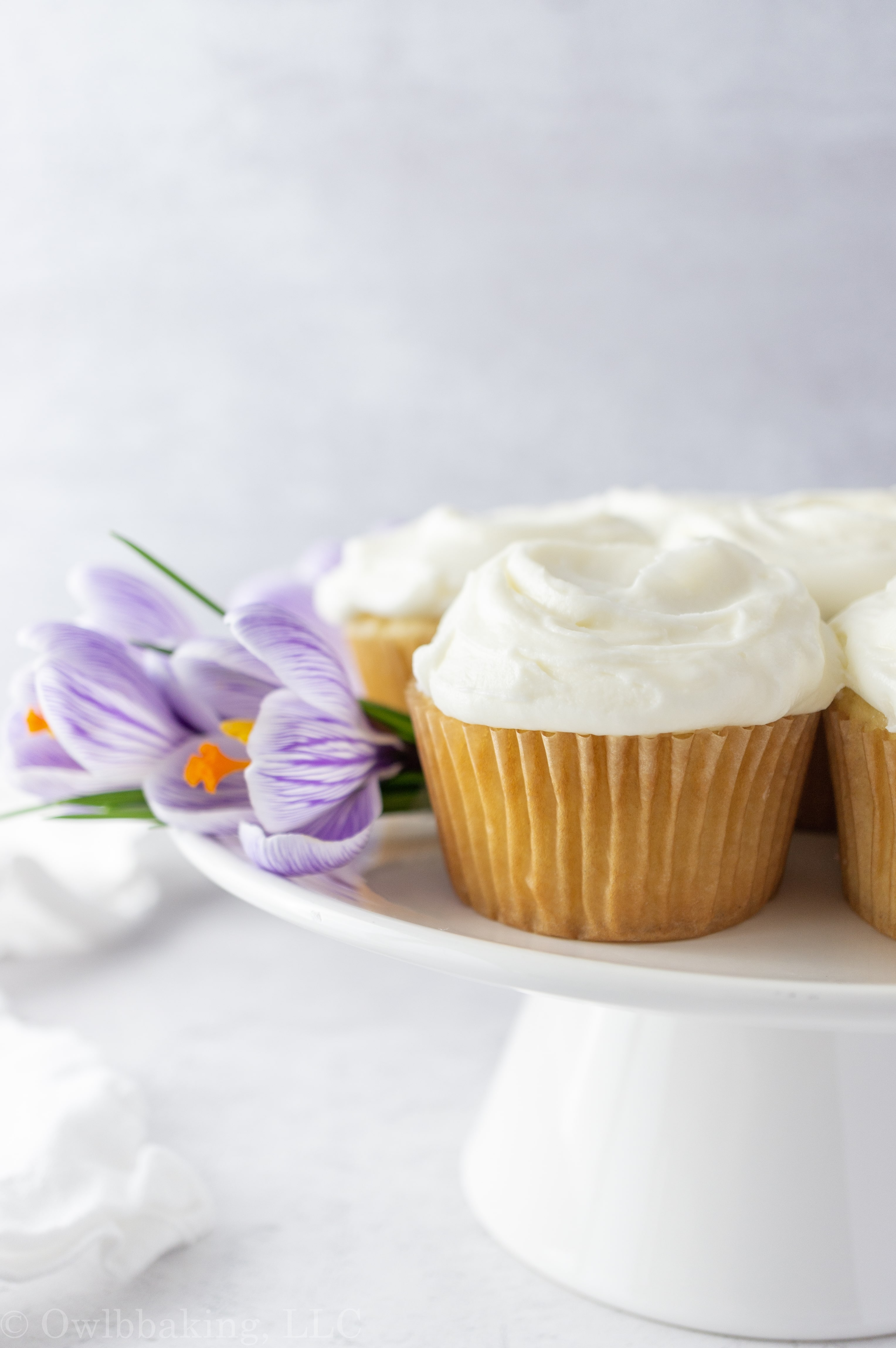cupcake on cake stand with a purple flower